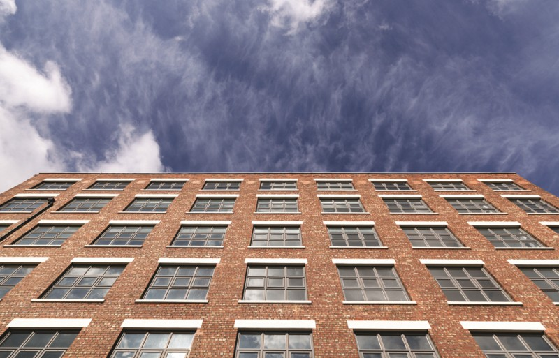 red brick building with square windows and blue sky
