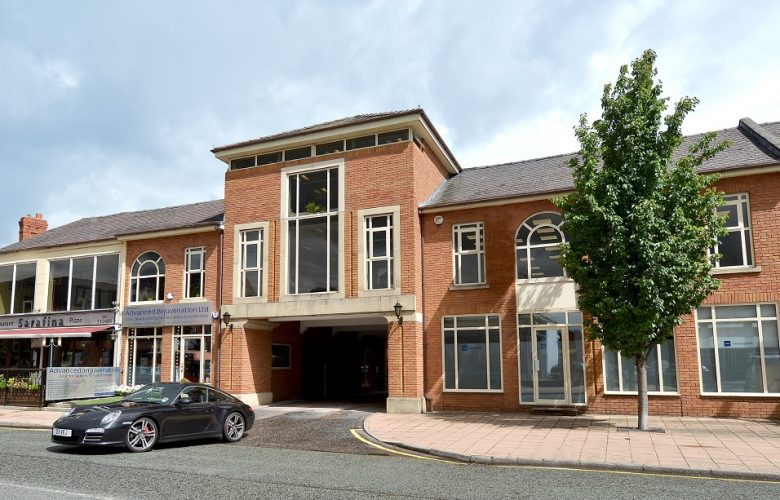 red brick office buildng with porsche driving out of car park